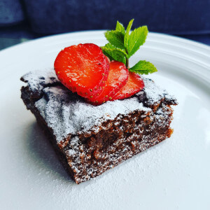 Chickpea blondie topped with fresh strawberries and mint.