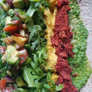 Colourful hummus, tomato and avocado wrap.