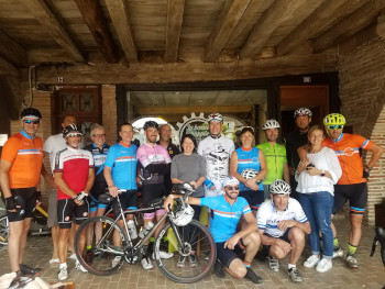 A group of cyclists pose for a photograph outside La Bonne Echappée.