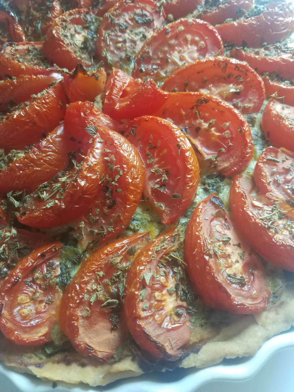 Finished leek and dill quiche topped with roasted tomatoes and oregano.