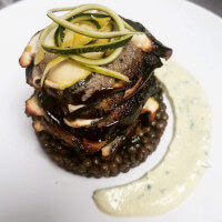 Aubergine and courgette stack on a bed of puy lentils with a parsley and lemon sauce.