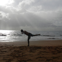 A man does a yoga pose on a beach as the sun begins to set.