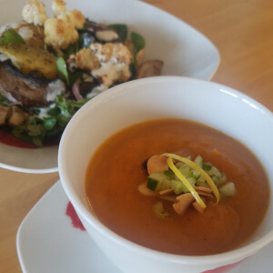 Soup in a teacup with a crunchy cucumber, almond and lemon zest garnish.